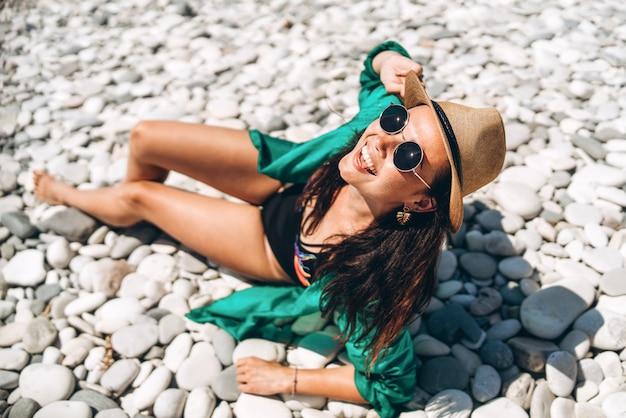 Asiatisches reisemädchen der hübschen wanne, das auf dem strand in dem meer in grünem pareo sich entspannt.