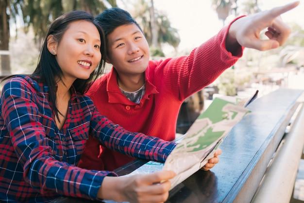 Asiatisches reisendes paar, das eine karte hält und nach wegbeschreibungen sucht.