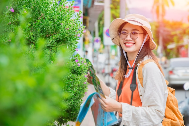 Asiatisches reisendesmädchen jugendlich oder tourist glückliches lächeln reisen in den sommerferien mit kartenspaziergang auf der straße