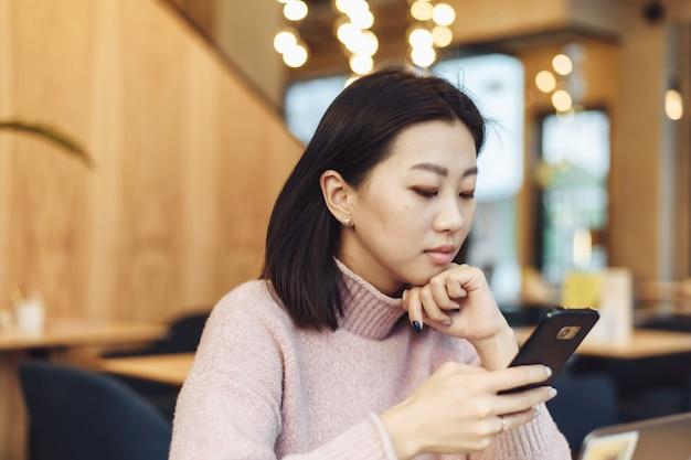 Asiatisches reizendes mädchen klettern am telefon in einem café. eine hübsche schöne frau sucht im internet nach informationen oder arbeitet