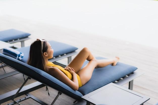 Asiatisches schönes glückliches lächeln der jungen frau des porträts entspannen sich um swimmingpool im freien in den feiertagsferien
