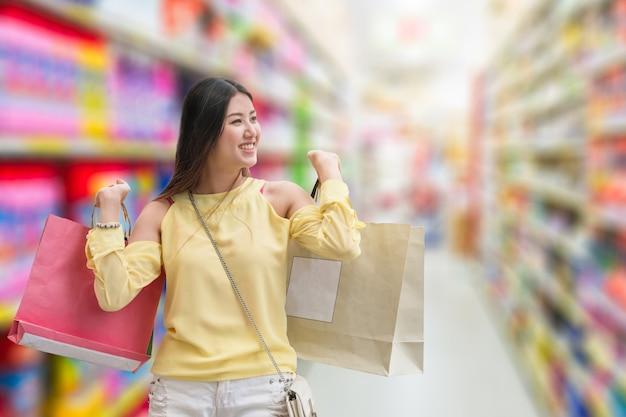 Asiatisches schönheitsmädchen ist glück mit papiertüten auf verschwommenem gassenkaufhaus