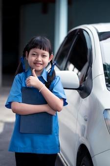 Asiatisches schulmädchen, das ein buch mit stehender seite des autos hält. zurück zum schulkonzept
