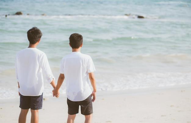 Asiatisches schwules paar, das hände zusammen am strand hält.