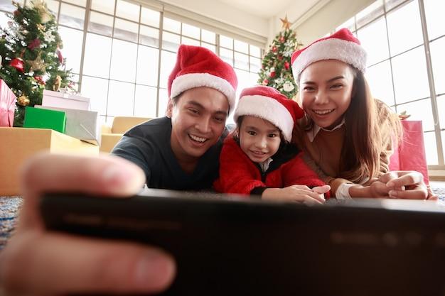Asiatisches selfie, das smartphone hält foto aufnehmen. glückliche junge familie mit kinderspaß beim feiern von weihnachten. weihnachtszeit. mein vater, meine mutter und meine tochter in weihnachtsmützen liegen zu hause vor der geschenkbox herum.
