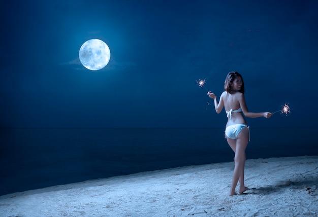 Asiatisches sexy mädchen im bikini, der feuerwerke auf dem strand nachts hält