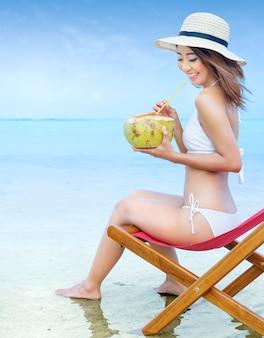 Asiatisches sexy mädchen im bikini und im hut mit kokosnuss tragen beim sitzen auf dem strandstuhl an der küste früchte