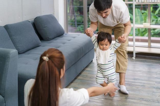 Asiatisches sohnbaby, das erste schritte macht, geht vorwärts zu seiner mutter. glückliches kleines baby, das lernt, mit hilfe des vaters zu gehen und lehrt, wie man sanft nach hause geht