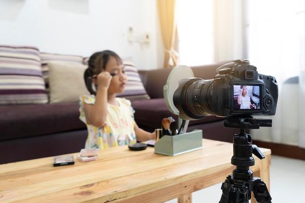 Asiatisches spiel des kleinen mädchens, das ein make-up mit der aufnahme macht videoblogger-kamera macht