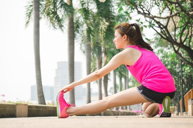 Asiatisches sportfrauenaufwärmen für das laufen und yoga im park