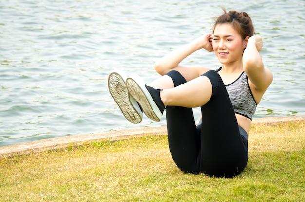 Asiatisches sportfrauenaufwärmen, zum auf grünen rasen zu trainieren