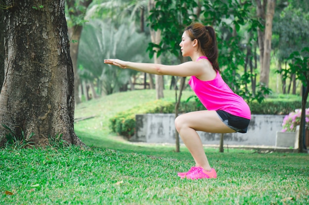 Asiatisches sportfrauenaufwärmen, zum durch körpergewichtshocke im park zu trainieren