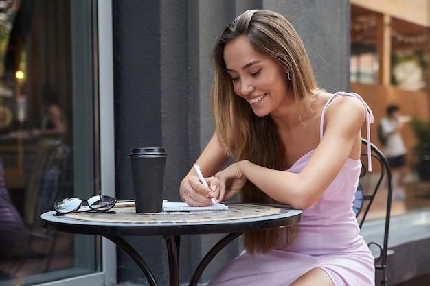 Asiatisches studentenmädchen mit tasse kaffee außerhalb des cafés, das hausaufgaben macht