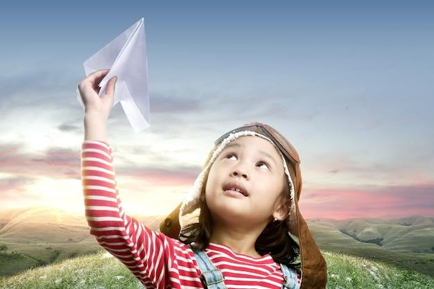 Asiatisches süßes mädchen in einer fliegermütze mit einem papierflugzeug mit einem sonnenuntergangshimmel