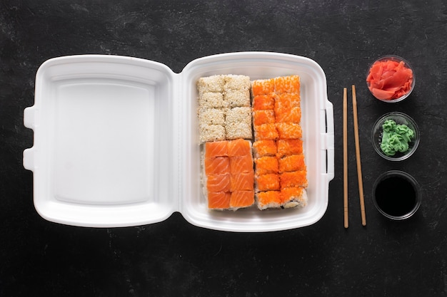 Asiatisches sushi in einem plastikbehälter auf einem schwarzen hintergrund
