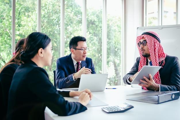 Asiatisches team des geschäftstreffens und arabischer mann, der seine ideen im büroraum darstellt