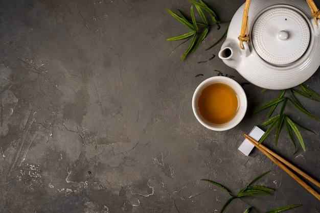 Asiatisches tee-konzept, tasse tee und teekanne mit grünem tee trockene blätter ansicht von oben, raum für einen text auf dunklem steinhintergrund