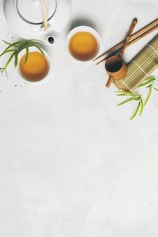 Asiatisches teekonzept, zwei weiße tassen tee, teekanne, teesatz, essstäbchen, bambusmatte umgeben mit trockenem grünem tee auf weißem hintergrund mit kopienraum. tee brauen und trinken.