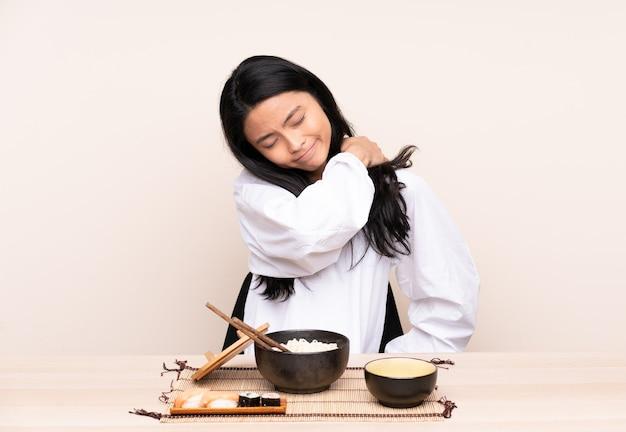 Asiatisches teenager-mädchen, das asiatisches essen isst, isoliert auf beige, das unter schmerzen in der schulter leidet, weil es sich bemüht hat