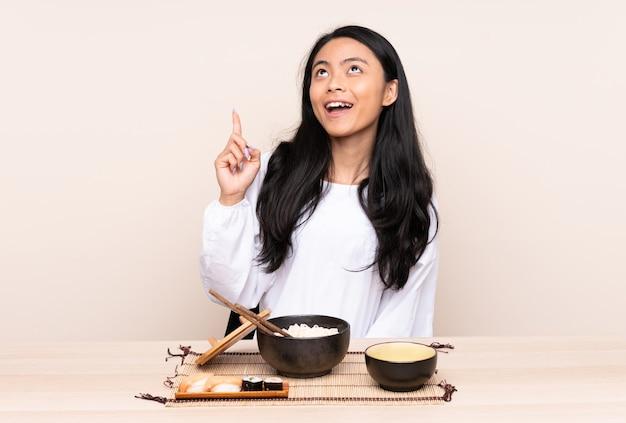Asiatisches teenager-mädchen, das asiatisches essen lokalisiert auf beige zeigt, das oben zeigt und überrascht