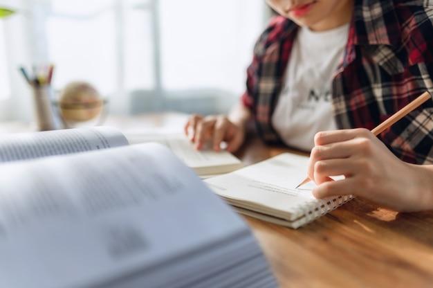 Asiatisches teenager-mädchen mit kopfhörern, das online sprache lernt, mit laptop, auf den bildschirm schaut, schulaufgaben zu hause erledigt, notizen schreibt, vorlesungen oder musik hört, fernunterricht Premium Fotos