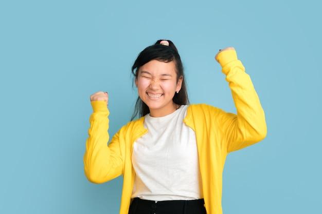 Asiatisches teenagerporträt lokalisiert auf blauem raum. schönes weibliches brünettes modell mit langen haaren