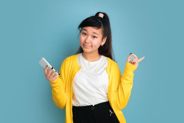 Asiatisches teenagerporträt lokalisiert auf blauem raum