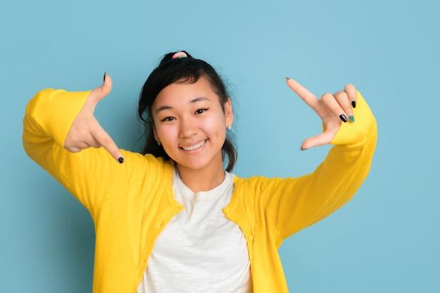 Asiatisches teenagerporträt lokalisiert auf blauem studiohintergrund. schönes weibliches brünettes modell mit langen haaren im lässigen stil. konzept der menschlichen emotionen, gesichtsausdruck, verkauf, anzeige. macht selfie.