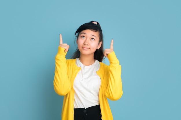 Asiatisches teenagerporträt lokalisiert auf blauem studiohintergrund. schönes weibliches brünettes modell mit langen haaren im lässigen stil. konzept der menschlichen emotionen, gesichtsausdruck, verkauf, anzeige. nach oben zeigend.