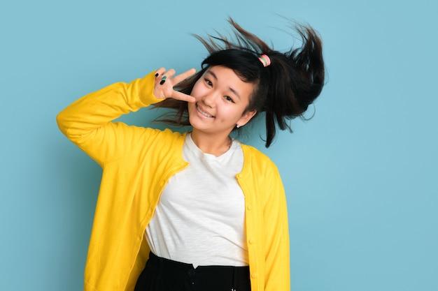 Asiatisches teenagerporträt lokalisiert auf blauem studiohintergrund. schönes weibliches brünettes modell mit langen haaren im lässigen stil. konzept der menschlichen emotionen, gesichtsausdruck, verkauf, anzeige. positiv posieren.