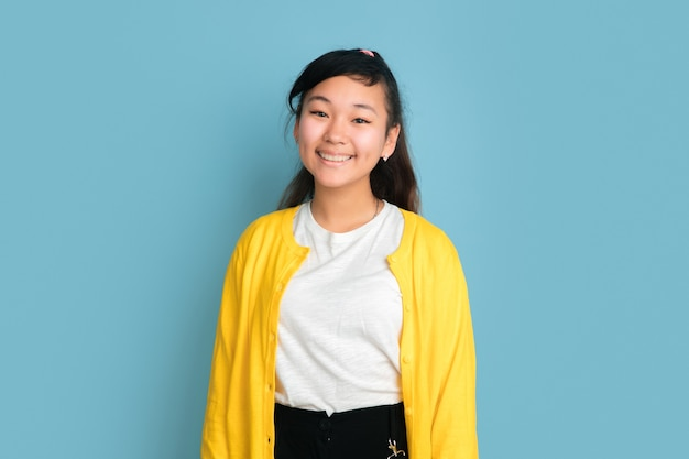 Asiatisches teenagerporträt lokalisiert auf blauem studiohintergrund. schönes weibliches brünettes modell mit langen haaren im lässigen stil. konzept der menschlichen emotionen, gesichtsausdruck, verkauf, anzeige. süß lächelnd.