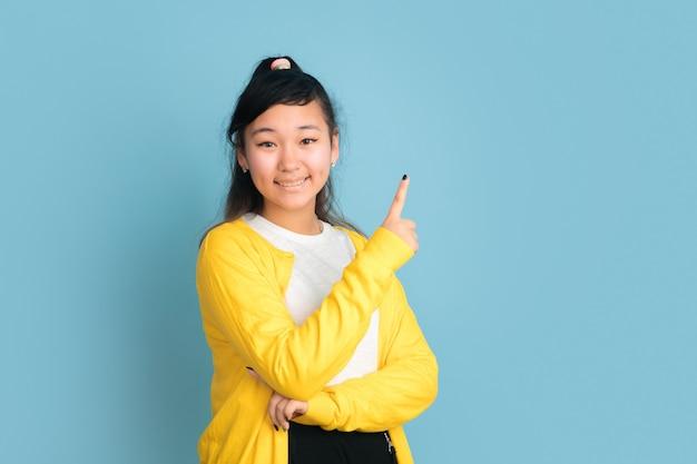 Asiatisches teenagerporträt lokalisiert auf blauem studiohintergrund. schönes weibliches brünettes modell mit langen haaren. konzept der menschlichen emotionen, gesichtsausdruck, verkauf, anzeige. lächeln, nach oben zeigen, sieht süß aus.