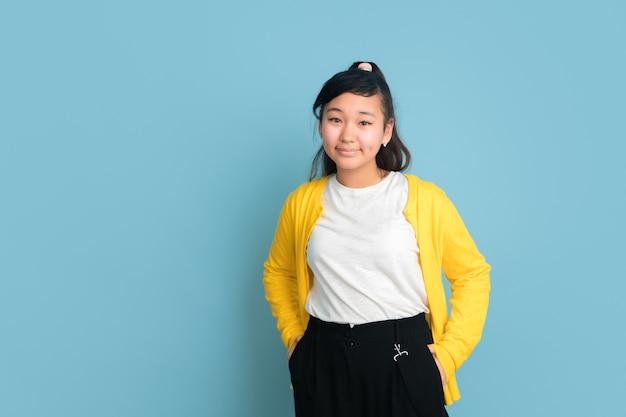 Asiatisches teenagerporträt lokalisiert auf blauem studiohintergrund. schönes weibliches brünettes modell mit langen haaren. konzept der menschlichen emotionen, gesichtsausdruck, verkauf, anzeige. posieren, sieht zuversichtlich aus.