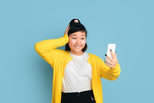 Asiatisches teenagerporträt lokalisiert auf blauem studiohintergrund