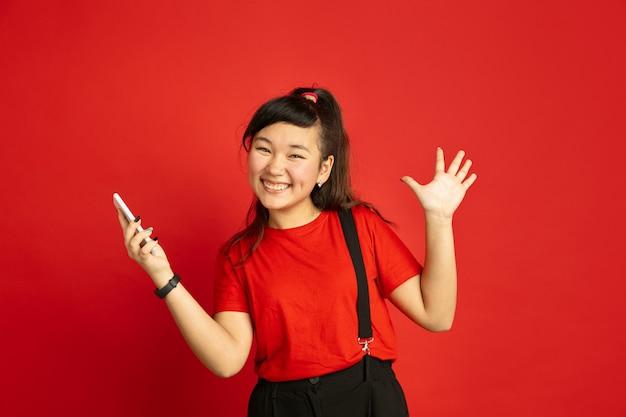 Asiatisches teenagerporträt lokalisiert auf rotem studiohintergrund. schönes weibliches brünettes modell im lässigen stil. konzept der menschlichen emotionen, gesichtsausdruck, verkauf, anzeige. glücklich, smartphone halten.