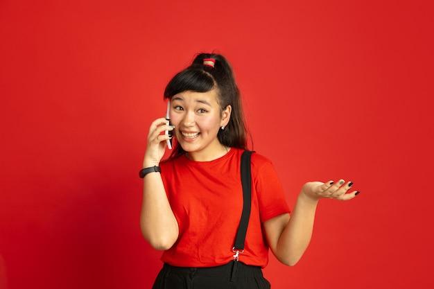 Asiatisches teenagerporträt lokalisiert auf rotem studiohintergrund. schönes weibliches brünettes modell mit langen haaren im lässigen stil. konzept der menschlichen emotionen, gesichtsausdruck, verkauf, anzeige. am telefon sprechen.