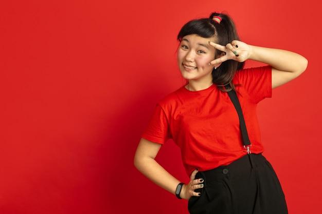 Asiatisches teenagerporträt lokalisiert auf rotem studiohintergrund. schönes weibliches brünettes modell mit langen haaren im lässigen stil. konzept der menschlichen emotionen, gesichtsausdruck, verkauf, anzeige. positiv posieren.