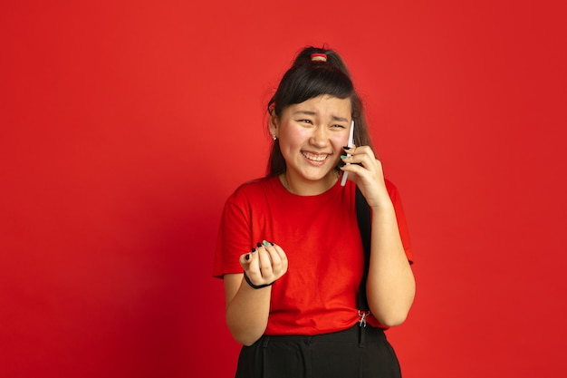 Asiatisches teenagerporträt lokalisiert auf rotem studiohintergrund. schönes weibliches brünettes modell mit langen haaren im lässigen stil. konzept der menschlichen emotionen, gesichtsausdruck, verkauf, anzeige. telefonieren.