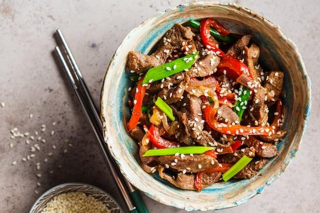 Asiatisches teriyaki-rindfleisch mit frühlingszwiebeln und sesam