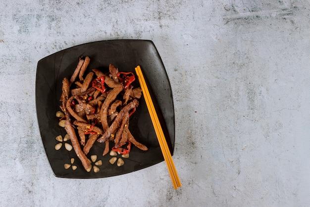 Asiatisches teriyaki rindfleisch mit glühenden pfeffern und essstäbchen.