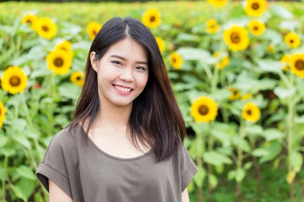 Asiatisches thailändisches jugendlich lächeln des netten porträts mit sonnenblume mit kopienraum.