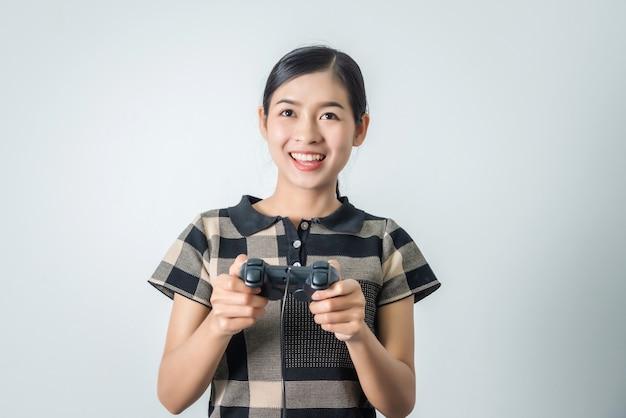Asiatisches thailändisches mädchen, das videospiel mit joystick spielt, glücksspielfrau glücklich.