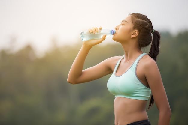 Asiatisches trinkwasser der jungen frau, nachdem sonnensatz gerüttelt worden ist