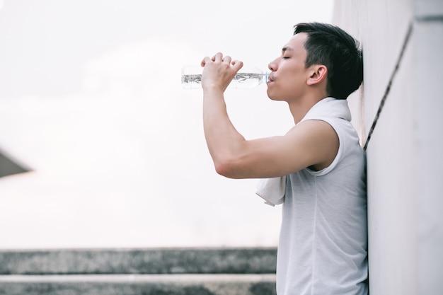 Asiatisches trinkwasser des jungen mannes nachdem dem rütteln