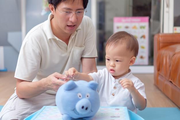 Asiatisches vater- und kleinkindjungenkind, das thailändische münze in blaues sparschwein steckt