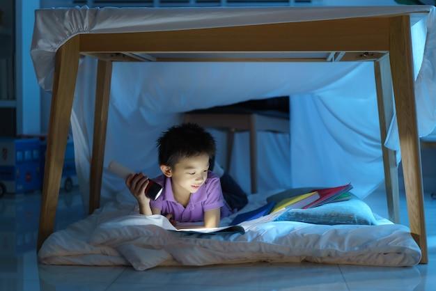 Asiatisches vorschulkind, um ein lager zu bauen, um fantasievoll zu spielen und buch mit taschenlampe im wohnzimmer zu hause zu lesen.