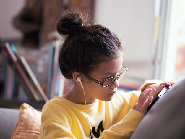 Asiatisches vorschulmädchen, das zu hause internetgeräte verwendetmädchen mit brille sitzt auf der couch und sucht nach datanerd culture