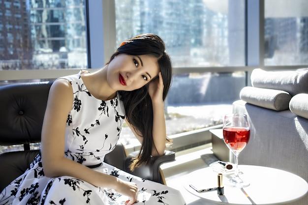 Asiatisches weibliches modell trägt ein modisches sexy weißes kleid