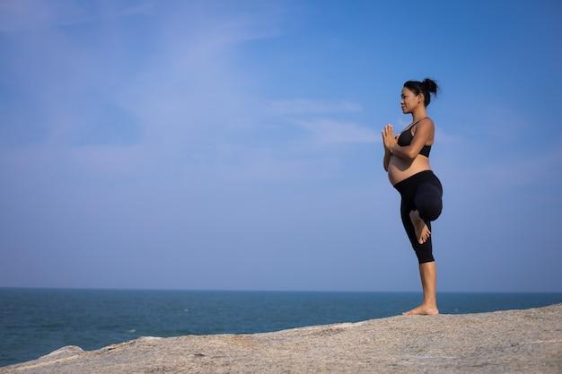 Asiatisches yoga der schwangeren frau auf der strandsonnenuntergang-sommerzeit