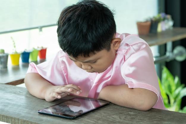 Asiatsjunge, der mit digitaler tablette spielt